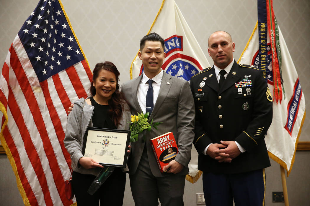 Anthony Hua, center, with his girlfriend Thuy Dihn, left, are photographed with U.S. Army Staff Sgt. Zachary Anderson, a health care recruiter, after getting sworn in as U.S. Army Reserve captain ...