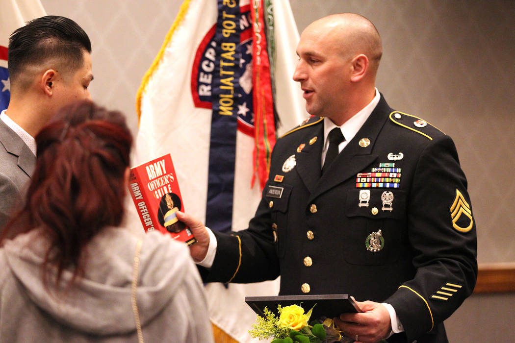 Anthony Hua receives a book as a gift from U.S. Army Staff Sgt. Zachary Anderson, a health care recruiter, after getting sworn in as U.S. Army Reserve captain during a ceremony at the Hampton Inn ...