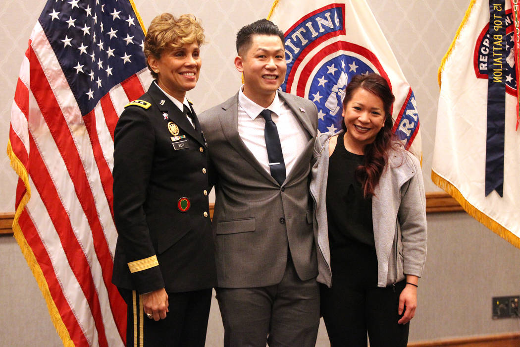 Anthony Hua, center, with his girlfriend Thuy Dihn, right, are photographed with U.S. Army Lt. Gen. Nadja West, after getting sworn in as captain for the U.S. Army Reserve during a ceremony at th ...
