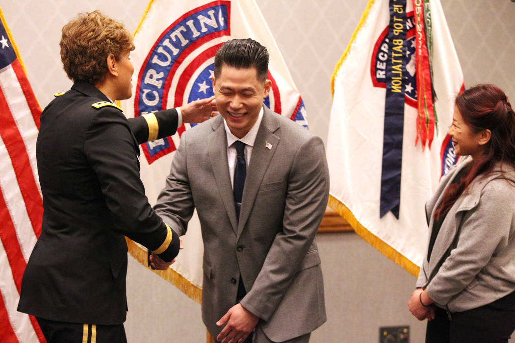 Anthony Hua, center, with U.S. Army Lt. Gen. Nadja West, left, and his girlfriend Thuy Dihn, smiles after getting sworn in as captain for the U.S. Army Reserve during a ceremony at the Hampton Inn ...