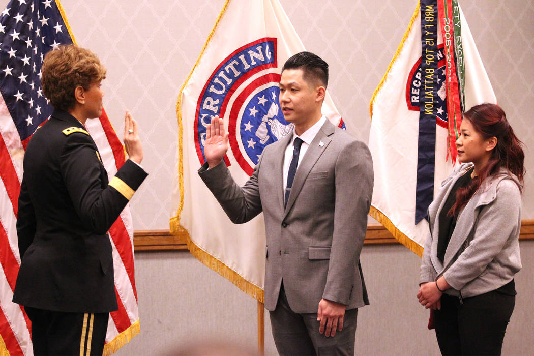 Anthony Hua, center, with U.S. Army Lt. Gen. Nadja West, left, and his girlfriend Thuy Dihn, is sworn in as captain for the U.S. Army Reserve during a ceremony at the Hampton Inn Tropicana and Eve ...