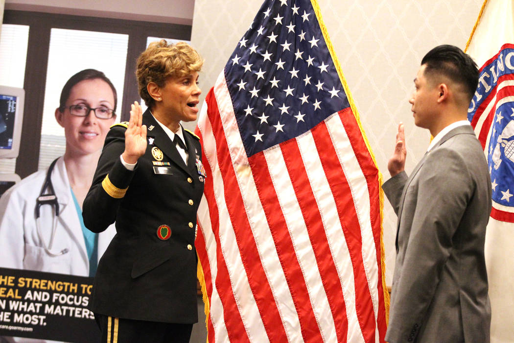 Anthony Hua, right, with U.S. Army Lt. Gen. Nadja West, is sworn in as captain for the U.S. Army Reserve during a ceremony at the Hampton Inn Tropicana and Event Center in Las Vegas, Friday, March ...