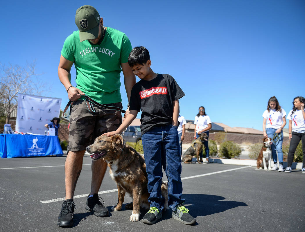 """Veteran Sheldon Moniz, left, and his son Xavier Moniz, 11, from Las Vegas stand with their new dog Warrior as the Nevada Department of Corrections partners with the """"Those Left Behind"""" F ..."""