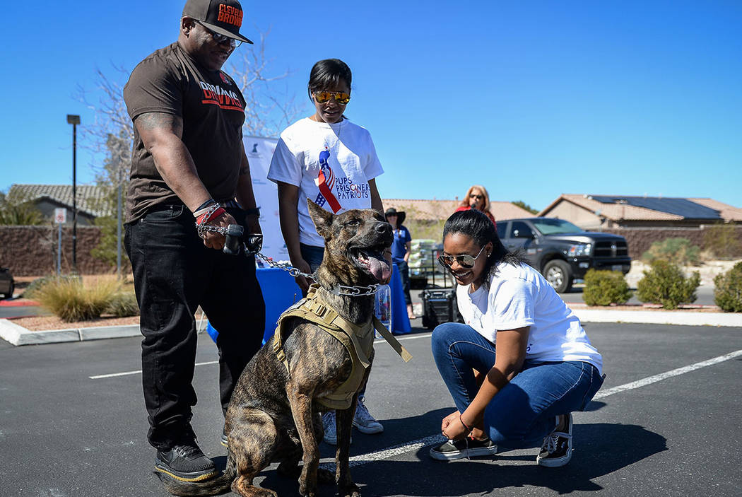 """Veteran Dale Malone, left, his twin daughters Nahjae Malone, 17 and Nia Malone, 17 from Las Vegas stand with their new dog Onyx as the Nevada Department of Corrections partners with the """"Thos ..."""