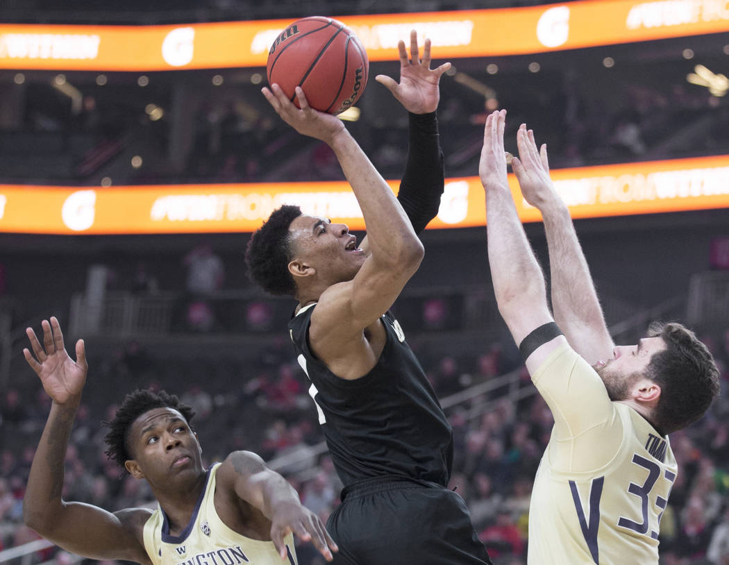 Colorado sophomore guard Tyler Bey (1) drives past Washington sophomore forward Nahziah Carter (11) and junior forward Sam Timmins (33) in the first half during the semifinal game of the Pac-12 t ...