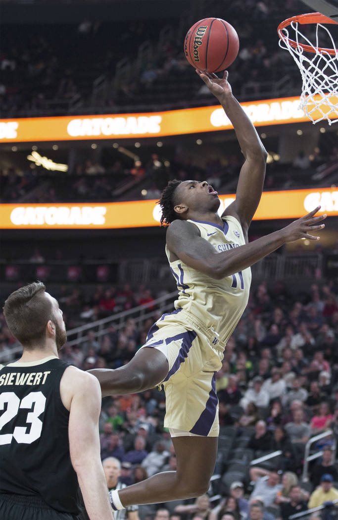 Washington sophomore forward Nahziah Carter (11) drives past Colorado junior forward Lucas Siewert (23) in the second half during the semifinal game of the Pac-12 tournament on Friday, March 15, 2 ...