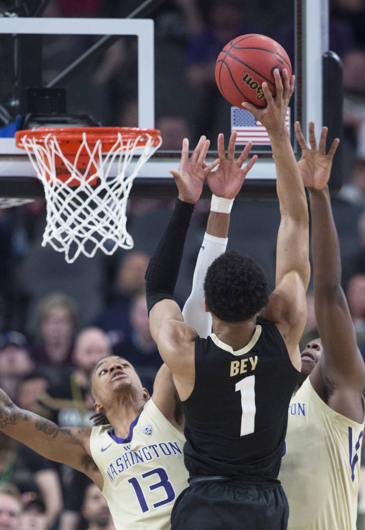 Washington sophomore forward Hameir Wright (13) and sophomore guard Jaylen Nowell (5) reach to block the shot of Colorado sophomore guard Tyler Bey (1) in the second half during the semifinal game ...