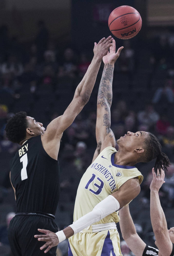Washington sophomore forward Hameir Wright (13) and Colorado sophomore guard Tyler Bey (1) fight for a loose ball in the second half during the semifinal game of the Pac-12 tournament on Friday, M ...