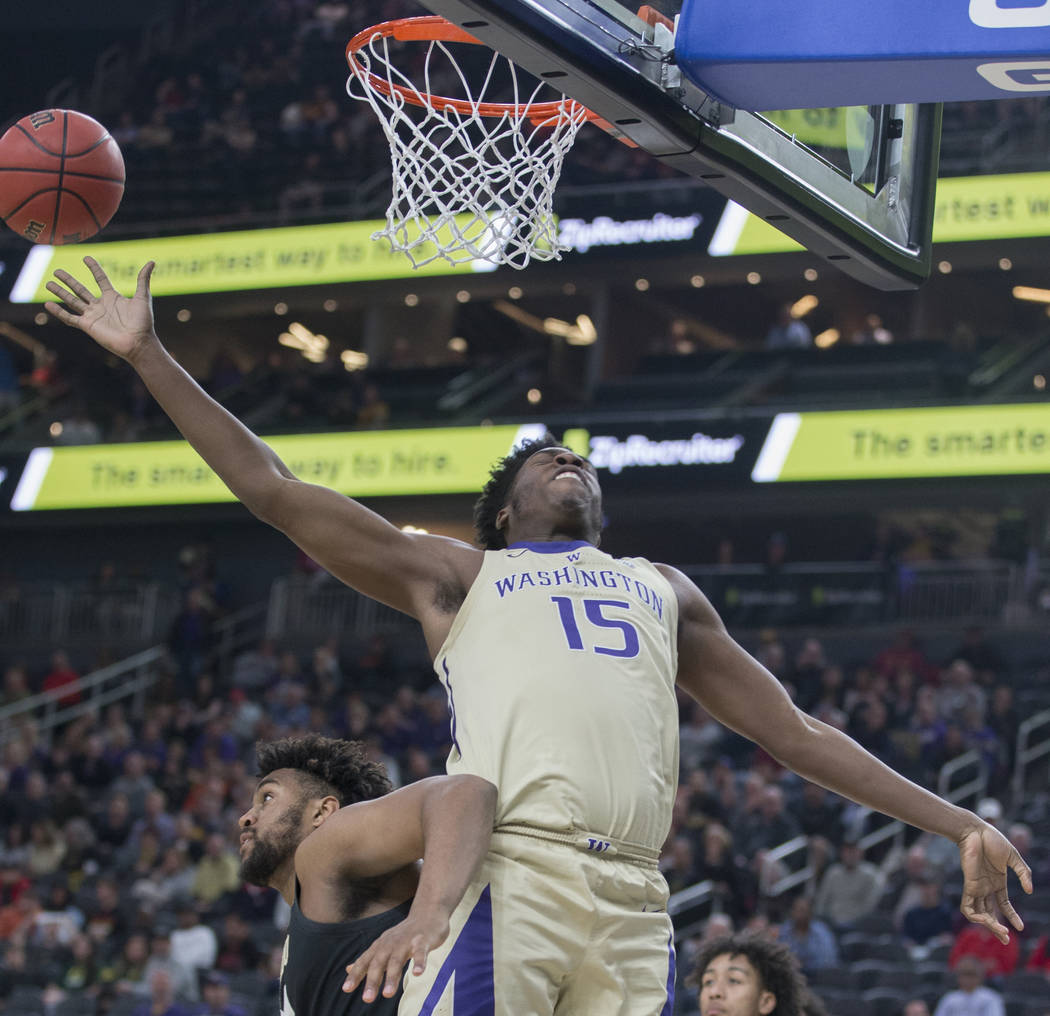 Washington senior forward Noah Dickerson (15) gets pushed by Colorado freshman forward Evan Battey (21) while trying to grab a rebound in the second half during the semifinal game of the Pac-12 to ...