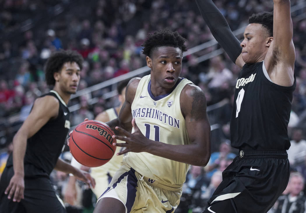 Washington sophomore forward Nahziah Carter (11) drives past Colorado junior guard Shane Gatling (0) in the second half during the semifinal game of the Pac-12 tournament on Friday, March 15, 2019 ...