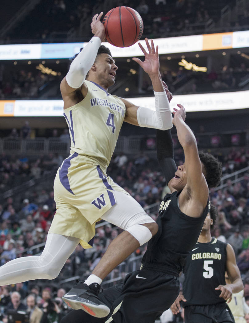 Washington senior guard Matisse Thybulle (4) collides with Colorado junior guard Shane Gatling (0) on the way to the rim in the second half during the semifinal game of the Pac-12 tournament on Fr ...