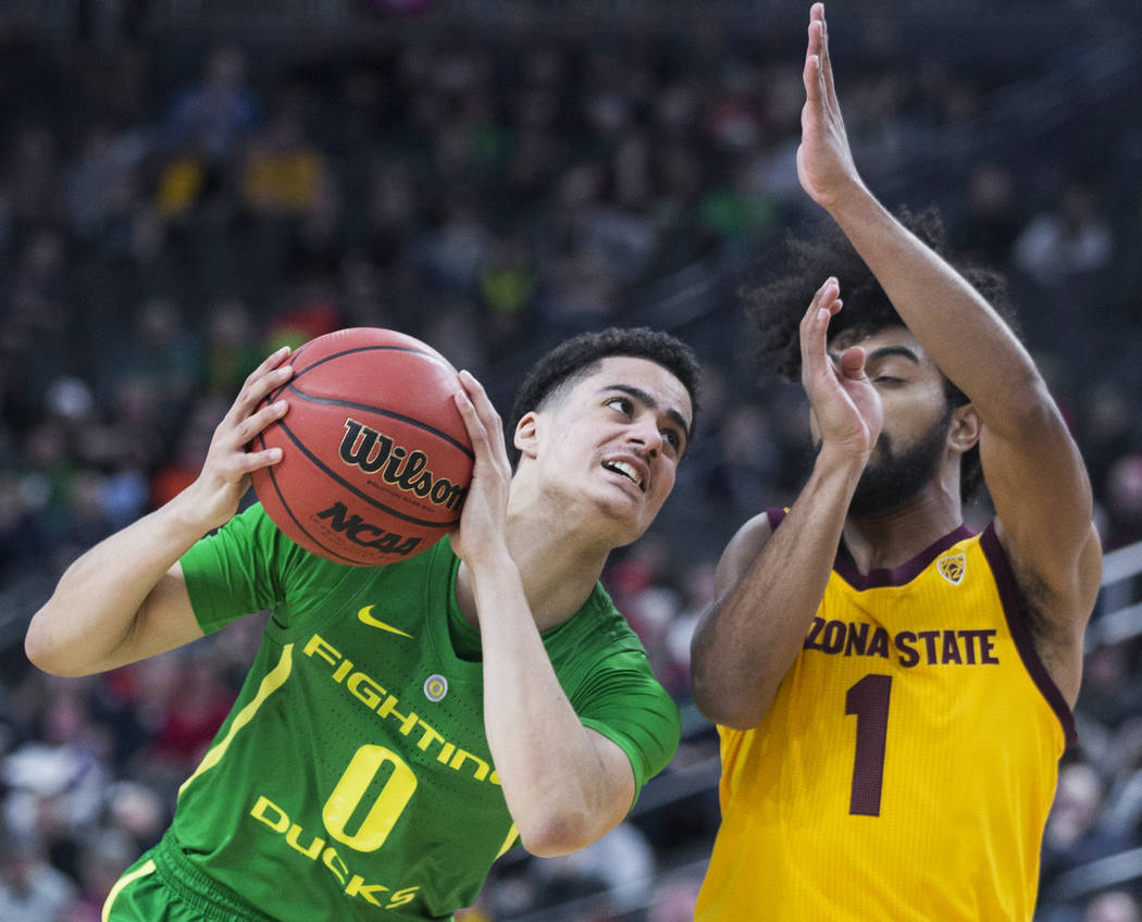Oregon freshman guard Will Richardson (0) drives past Arizona State sophomore guard Remy Martin (1) in the second half during the semifinal game of the Pac-12 tournament on Friday, March 15, 2019 ...