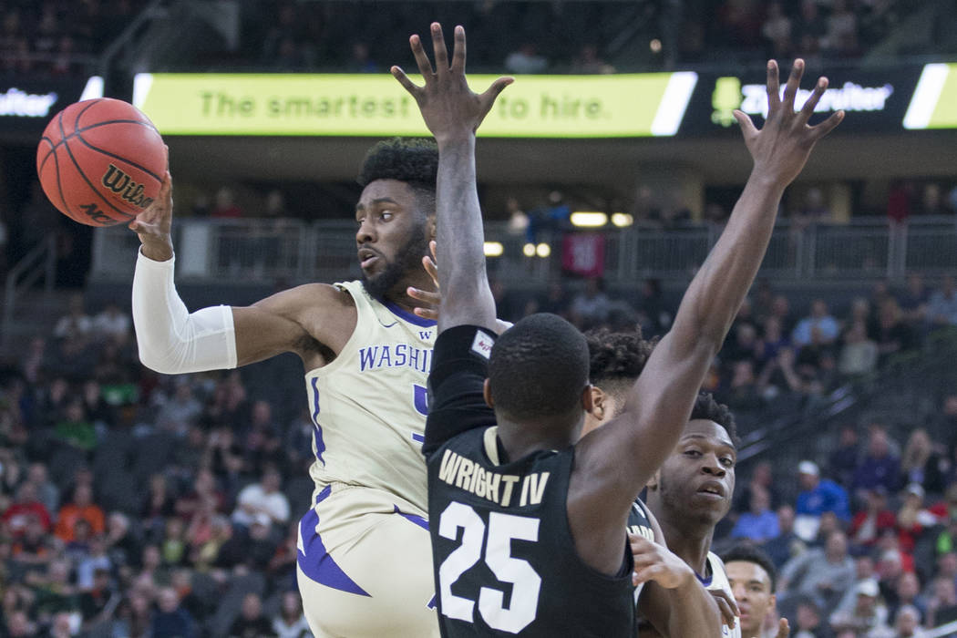 Washington sophomore guard Jaylen Nowell (5) dishes the ball past Colorado sophomore guard McKinley Wright IV (25) in the second half during the semifinal game of the Pac-12 tournament on Friday, ...
