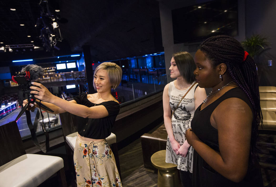 Cosplayer and influencer Stella Chuu, left, records video with grant recipients Giselle Colon, center, and Alesha DeBose while visiting the HyperX Esports Arena at the Luxor as part of the 1,000 D ...
