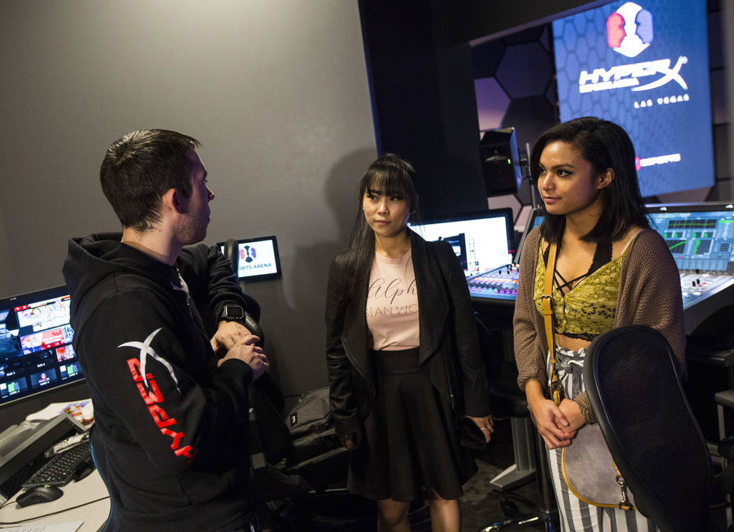 Austen Roberts, broadcast and media producer, talks with grant recipients Obe Wan, center, and Alexandra de la Cruz during a visit to the HyperX Esports Arena at the Luxor as part of the 1,000 Dre ...