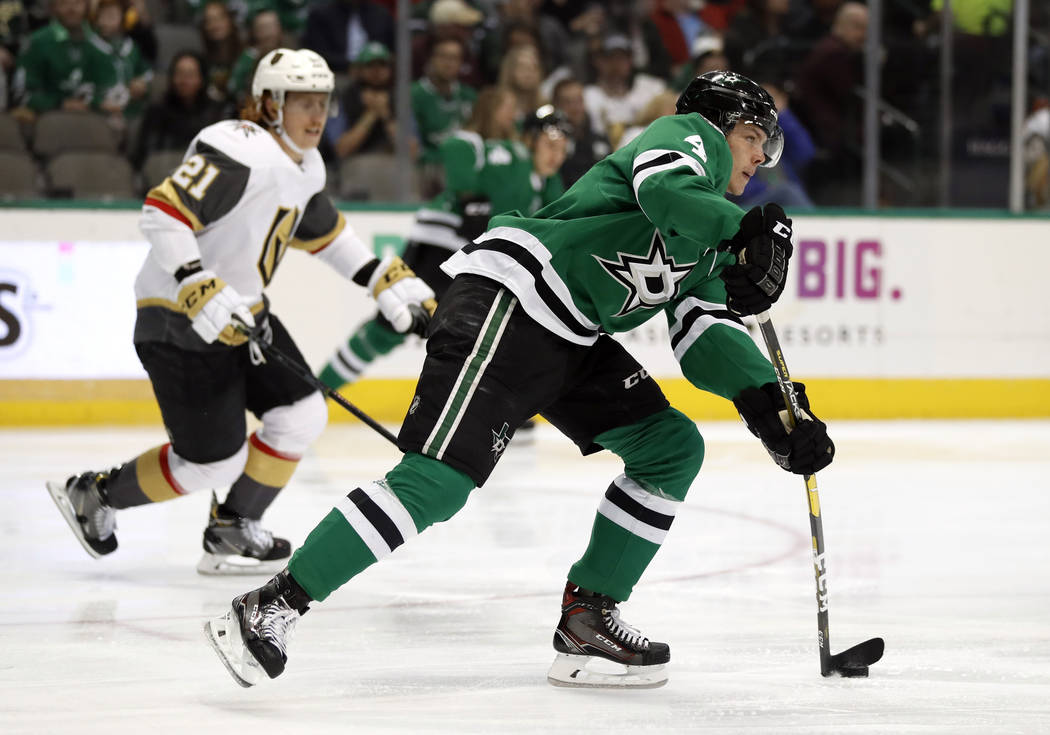 Dallas Stars defenseman Miro Heiskanen (4) handles the puck as Vegas Golden Knights' Cody Eakin (21) gives chase in the second period of an NHL hockey game in Dallas, Friday, March 15, 2019. (AP P ...