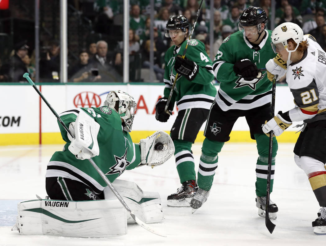 Dallas Stars goaltender Anton Khudobin (35) gloves a shot from the Vegas Golden Knights as Miro Heiskanen (4), Esa Lindell (23) and Cody Eakin (21) watch in the second period of an NHL hockey game ...
