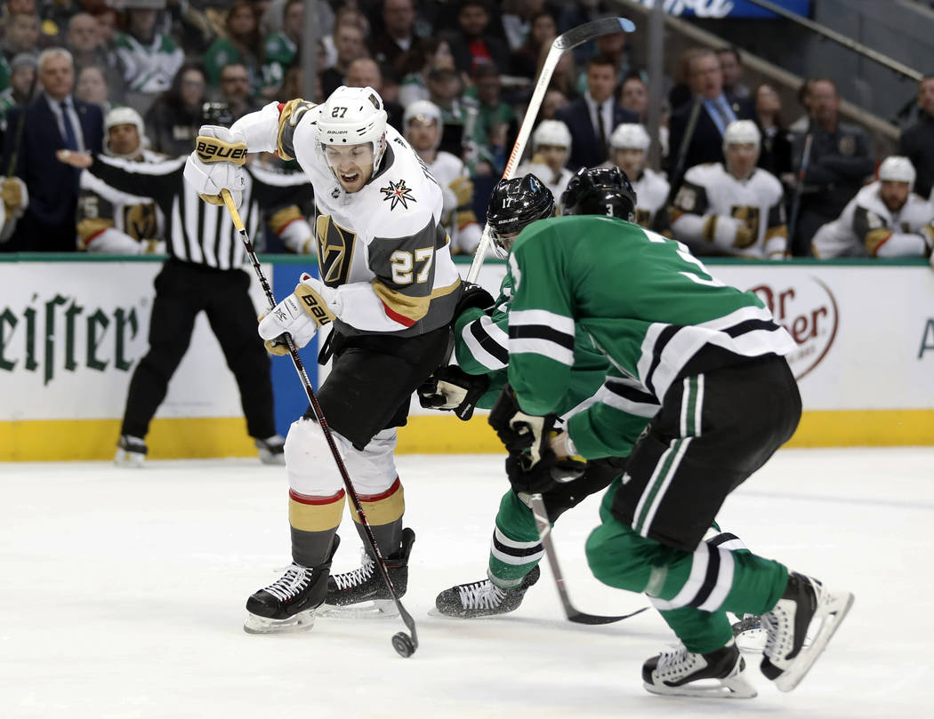 Vegas Golden Knights defenseman Shea Theodore (27) works to reach the net for a shot as Dallas Stars' Andrew Cogliano, rear, and John Klingberg (3) defend in the second period of an NHL hockey gam ...