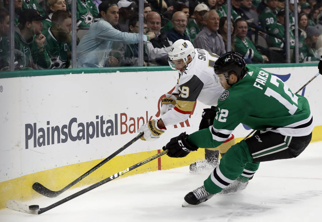 Vegas Golden Knights right wing Reilly Smith (19) and Dallas Stars center Radek Faksa (12) compete for control of the puck in the first period of an NHL hockey game in Dallas, Friday, March 15, 20 ...