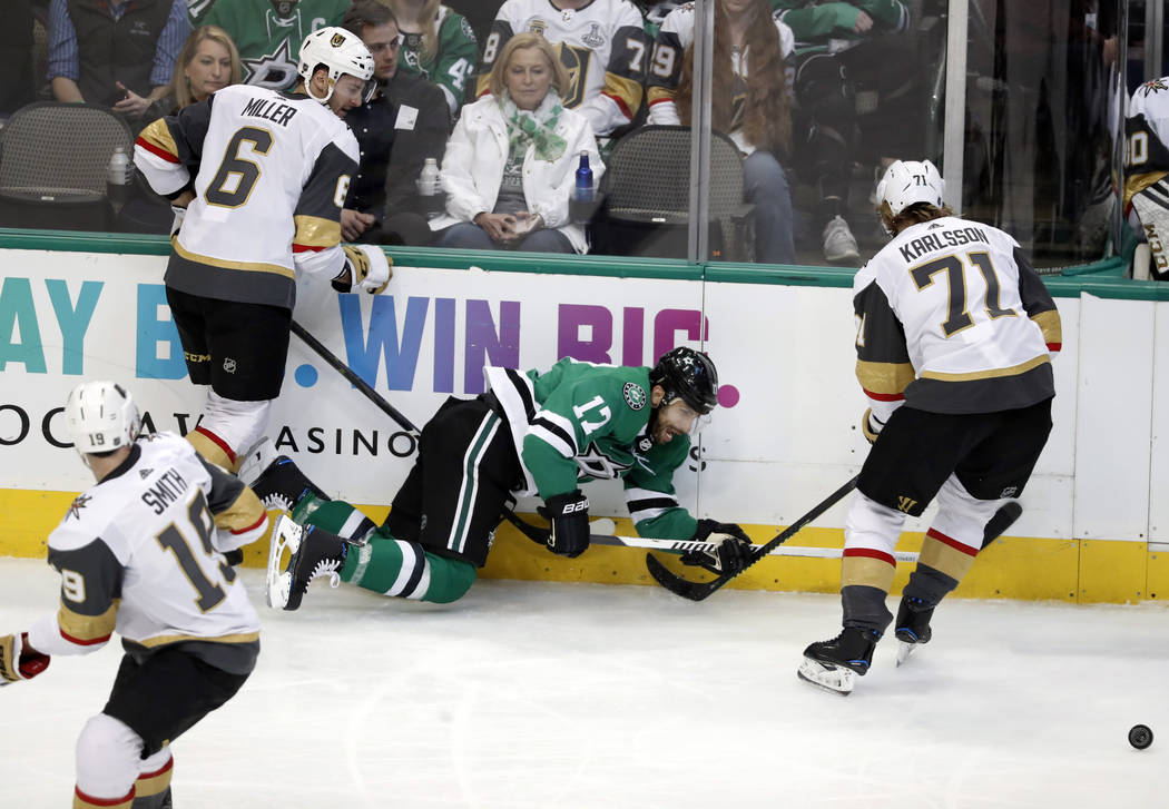 Dallas Stars center Andrew Cogliano (17) has the puck stripped away Vegas Golden Knights' Colin Miller (6) and William Karlsson (71) as Reilly Smith (19) watches in the third period period of an N ...
