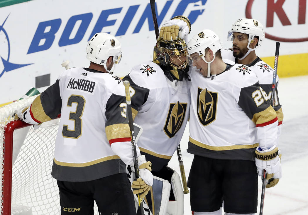 Vegas Golden Knights' Brayden McNabb (3), Paul Stastny (26) and Pierre-Edouard Bellemare, rear, celebrate with goalie Marc-Andre Fleury, second from left, after their 2-1 win against the Dallas St ...