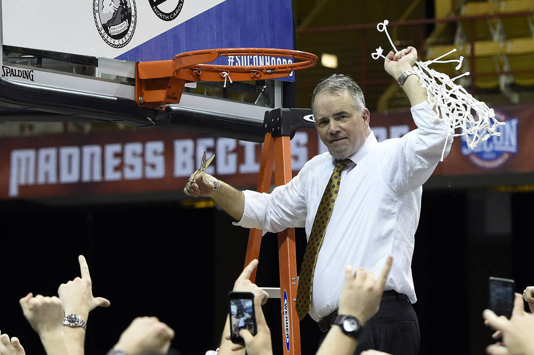 Wofford head coach Mike Young raises the basketball net in the air to celebrate his team's 70-58 win over UNC-Greensboro for the Southern Conference tournament championship, Monday, March 11, 2019 ...