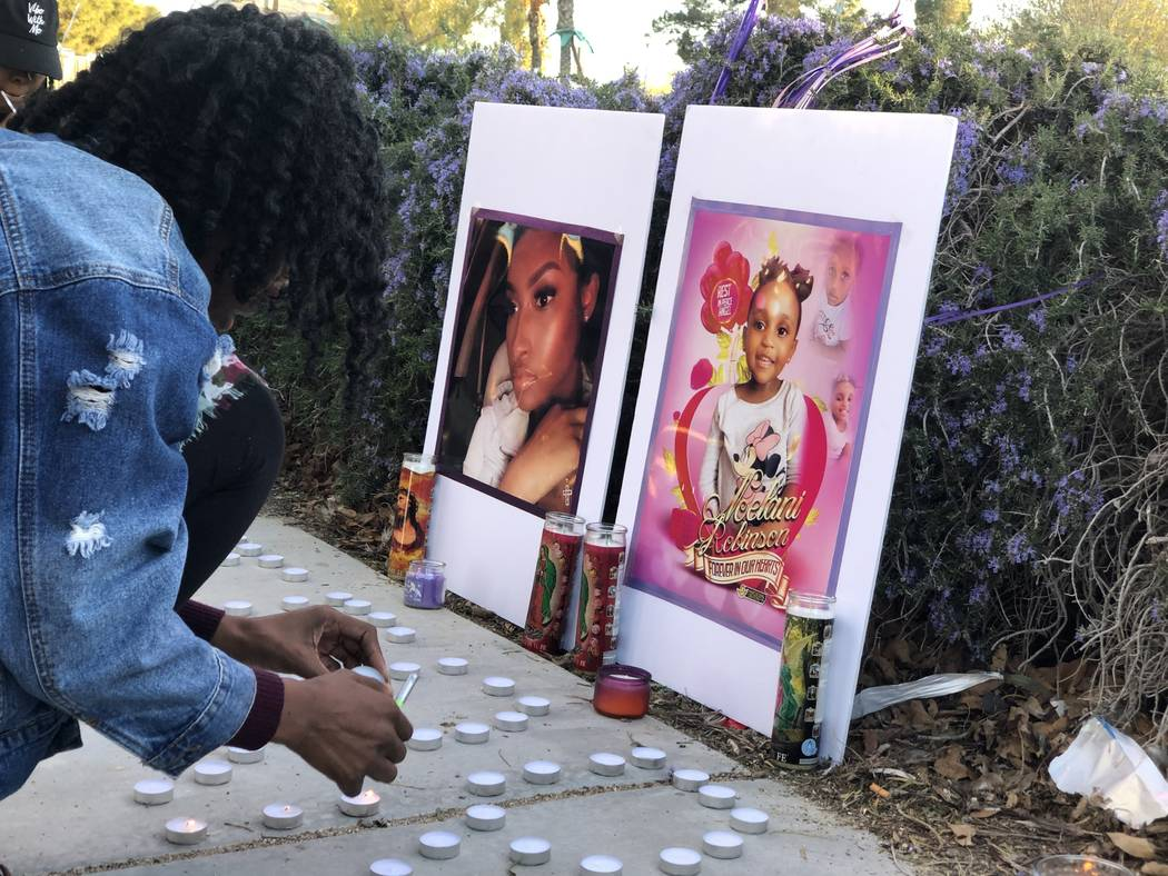 A woman lights a candle during a vigil on Saturday, March 16, 2019, in North Las Vegas for Sierra Robinson, 24, and her daughter, 2-year-old Noelani Robinson. Police said Sierra Robinson, of Las V ...