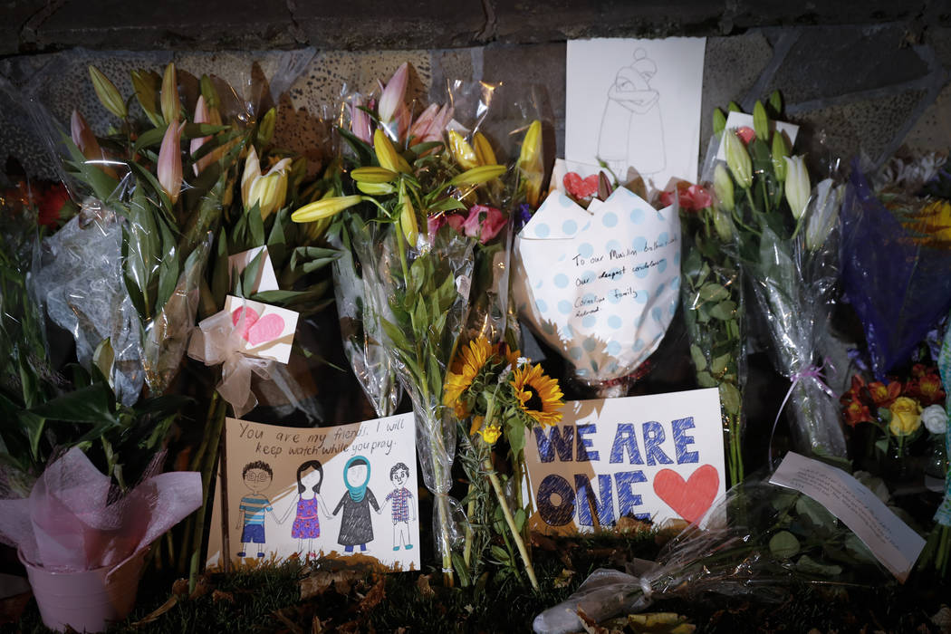 Mourners place flowers as they pay their respects at a makeshift memorial near the Masjid Al Noor mosque in Christchurch, New Zealand,, Saturday, March 16, 2019. New Zealand's stricken residents r ...