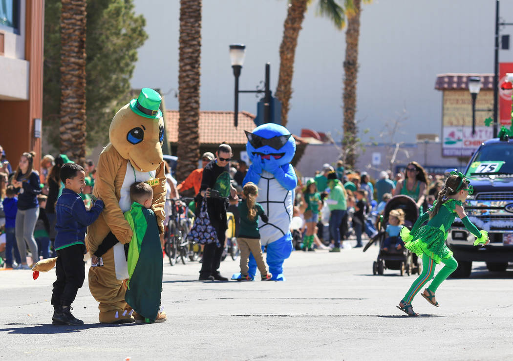 Children run out into the street during the parade to hug Charmander and Squirtel, two Pokemon, in the 53rd Annual Southern Nevada Sons & Daughters of Erin St. Patrick's Day parade in Henderso ...