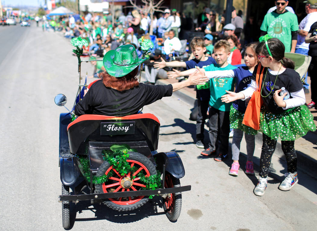 Cheri Delarosa, with the Ladies Oriental Shrine of North America Zel-Neva Court 96, gives out high fives in the 53rd Annual Southern Nevada Sons & Daughters of Erin St. Patrick's Day parade in ...
