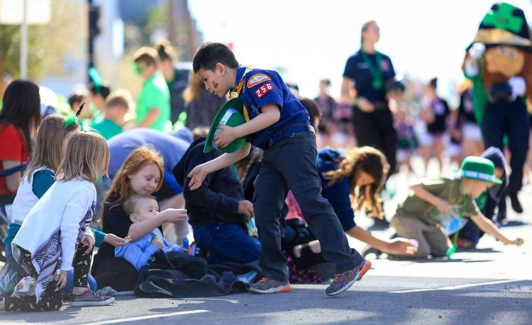 Cub Scout Jayden Riano, center, with Pack 256, lags behind his group as he takes time to make sure each kid gets a piece of candy in the 53rd Annual Southern Nevada Sons & Daughters of Erin St ...