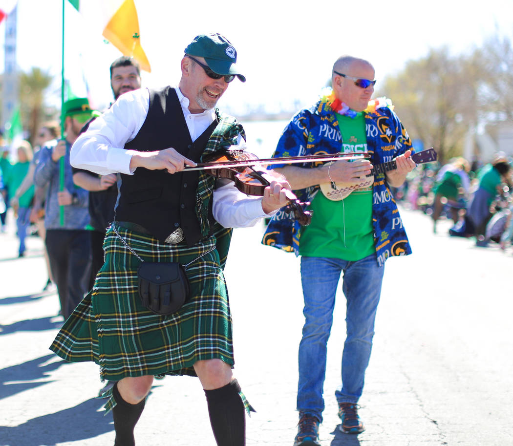 Digger Hawkins, left, and Jeff Bartholomew, right, both with Grape Expectations Nevada School of Winemaking, walk in the 53rd Annual Southern Nevada Sons & Daughters of Erin St. Patrick's Day ...