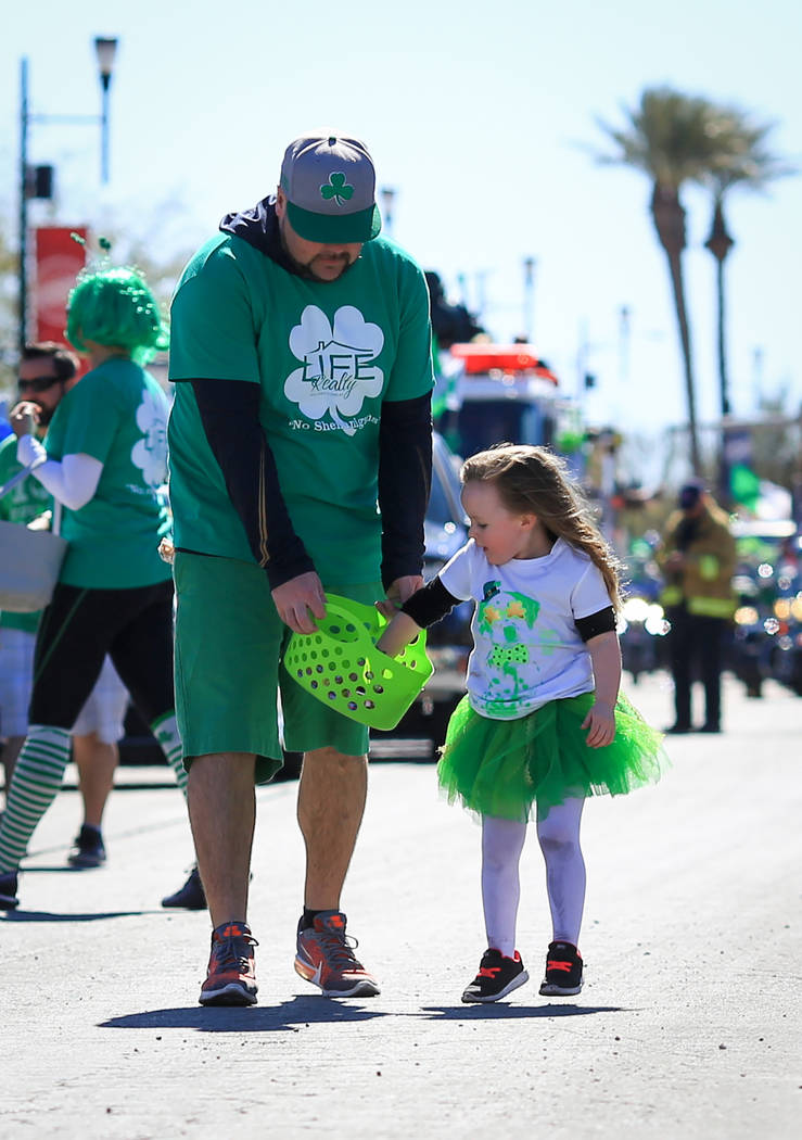 Brooke Leaver gets a refill of candy to throw to parade goers from her dad Bill Leaver, 37, in the 53rd Annual Southern Nevada Sons & Daughters of Erin St. Patrick's Day parade in Henderson, N ...