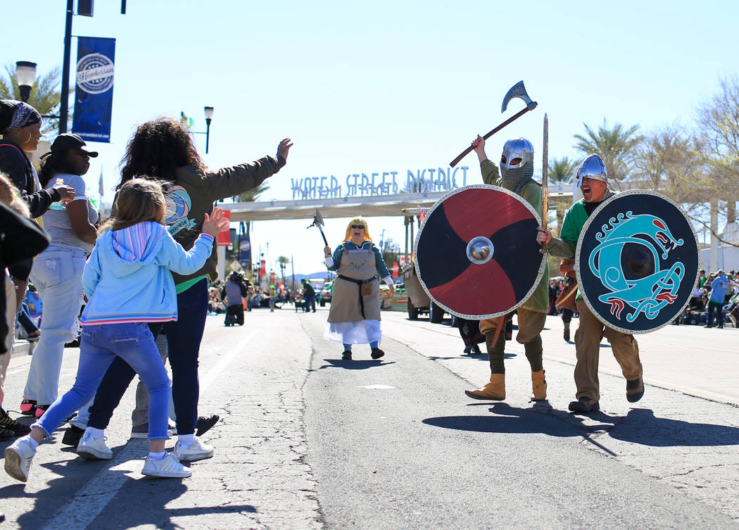 Brian Troxel, far right, and Erik Pappa, center right, with the Sons of Norway, jokingly charge at parade goers lining the streets of the 53rd Annual Southern Nevada Sons & Daughters of Erin S ...