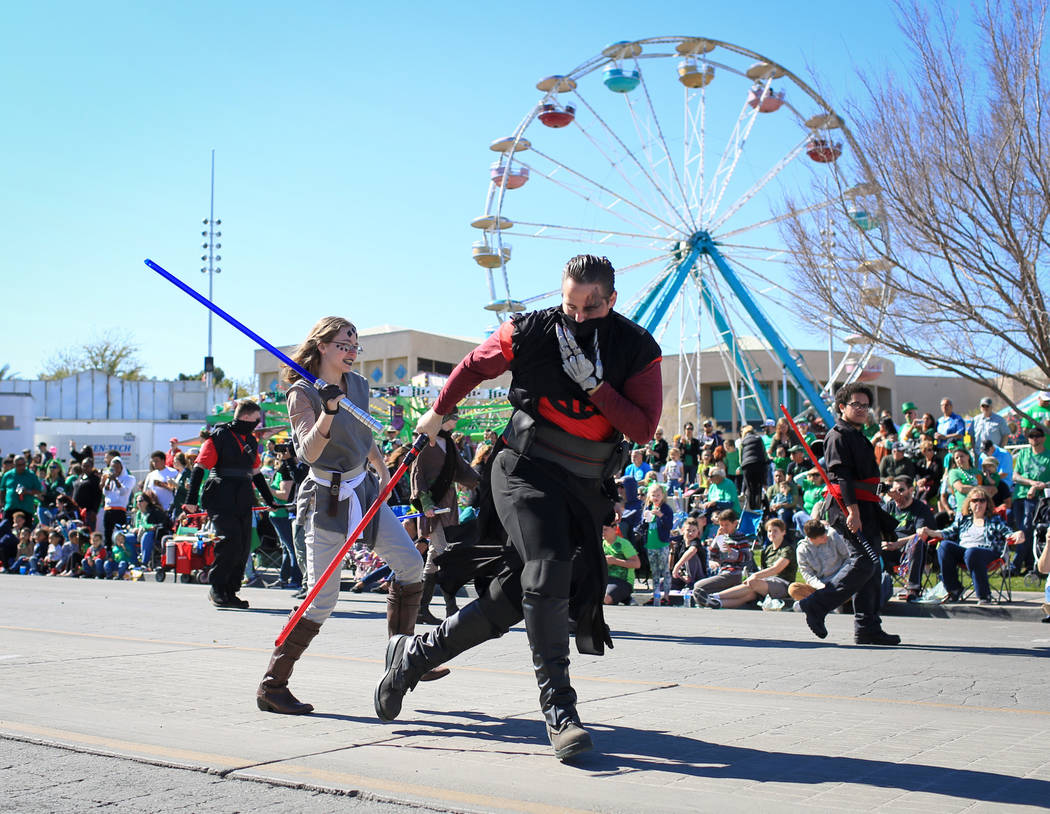 Two members of the Society of Light-saber Duelists UNLV chapter break into a fight during the 53rd Annual Southern Nevada Sons & Daughters of Erin St. Patrick's Day parade in Henderson, Nev., ...