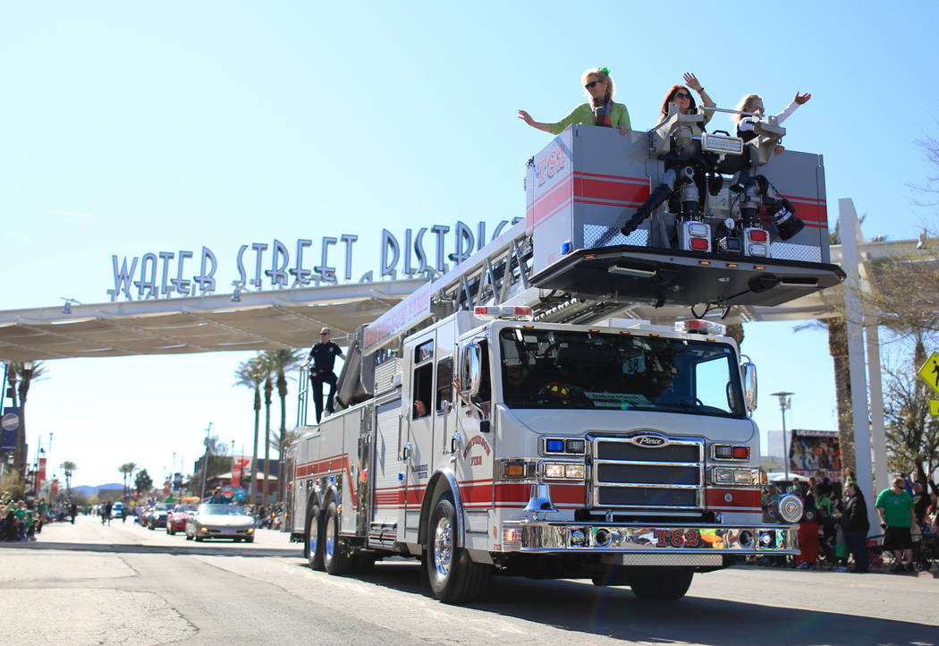 Henderson city mayor Debra March, middle in fire truck basket, waves to the crowd in the 53rd Annual Southern Nevada Sons & Daughters of Erin St. Patrick's Day parade in Henderson, Nev., on Sa ...