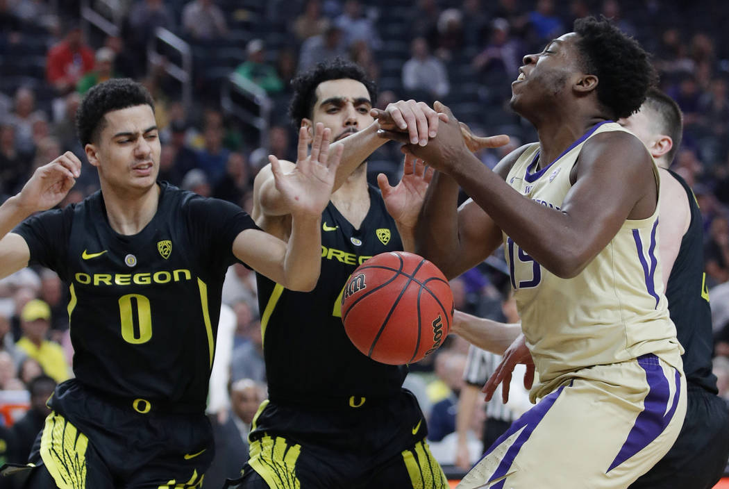 Oregon's Will Richardson, left, and Ehab Amin guard Washington's Noah Dickerson during the first half of an NCAA college basketball game in the final of the Pac-12 men's tournament Saturday, March ...