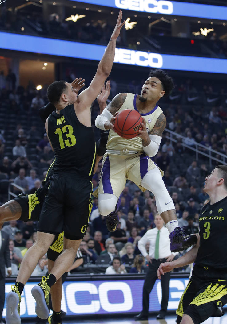 Washington's David Crisp shoots around Oregon's Paul White during the first half of an NCAA college basketball game in the final of the Pac-12 men's tournament Saturday, March 16, 2019, in Las Veg ...