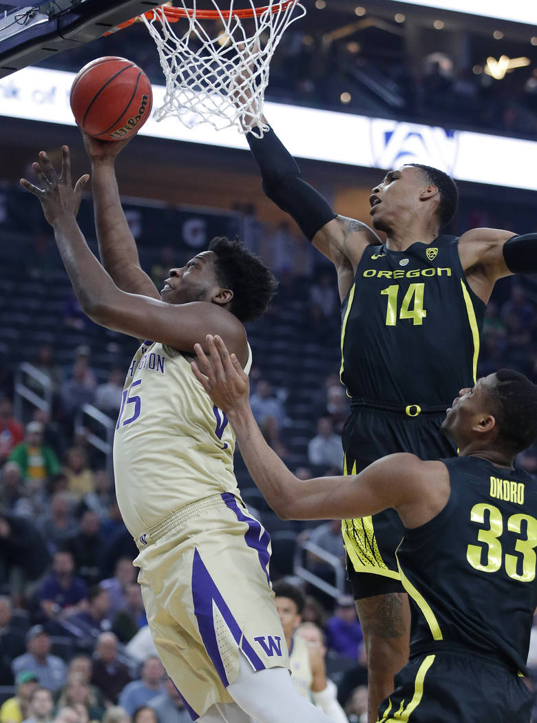 Washington's Noah Dickerson shoots around Oregon's Kenny Wooten (14) and Francis Okoro during the first half of an NCAA college basketball game in the final of the Pac-12 men's tournament Saturday ...