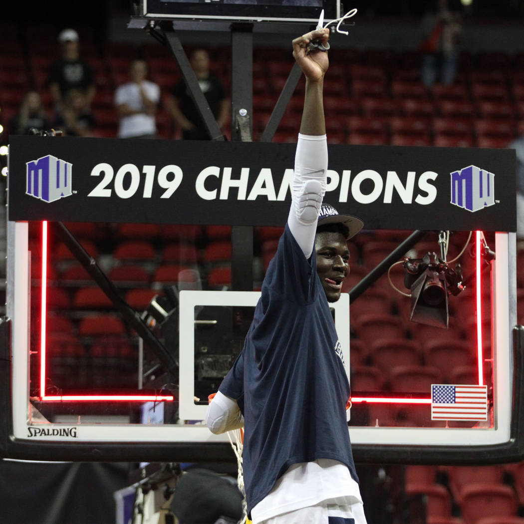 Utah State Aggies center Neemias Queta (23) raises a piece of a net after winning against San Diego State Aztecs in the Mountain West tournament men's basketball championship game at the Thomas &a ...