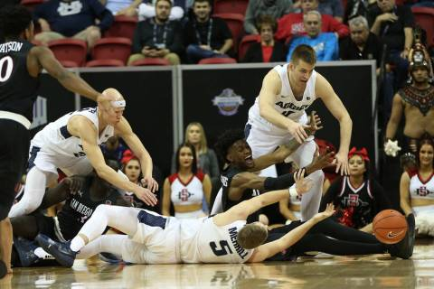 Utah State Aggies and San Diego State Aztecs fight for a loss ball in the second half of the Mountain West tournament men's basketball championship game at the Thomas & Mack Center in Las Vega ...