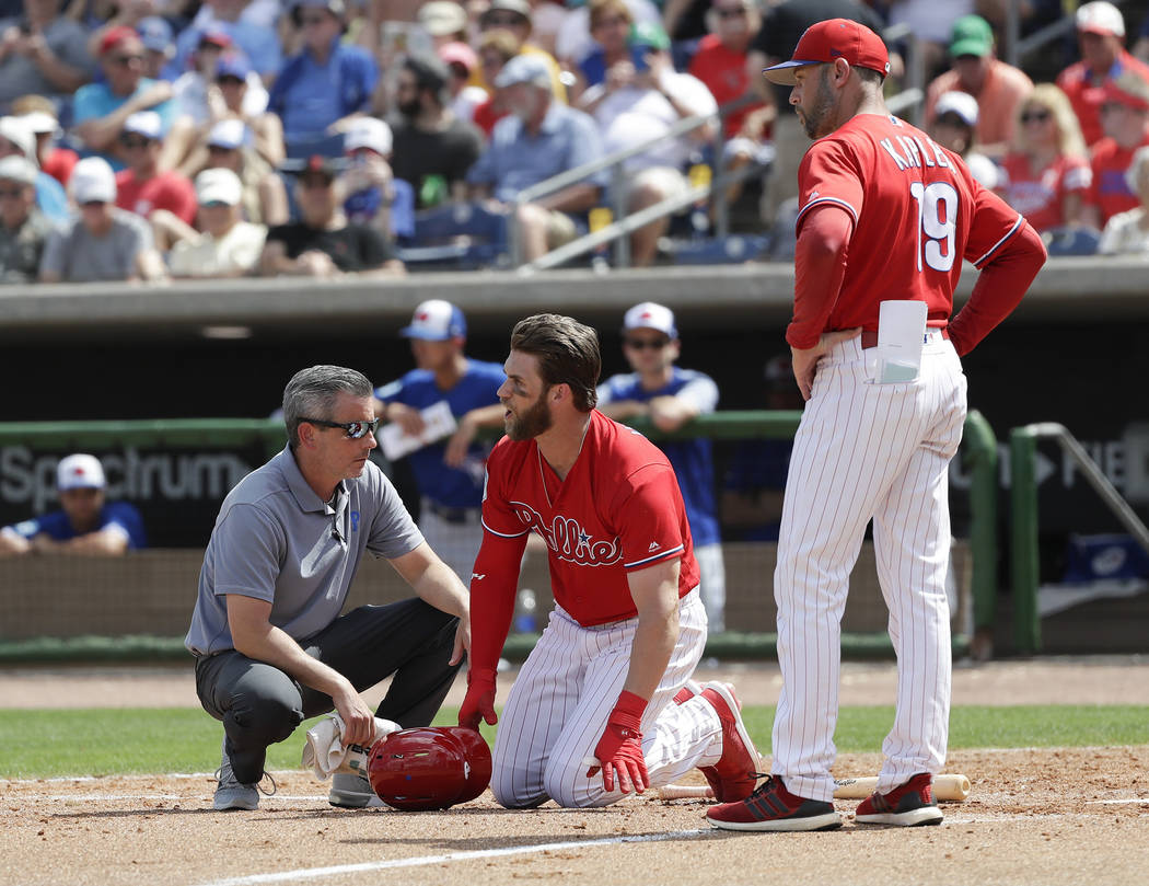 Philadelphia Phillies' Bryce Harper, center, yells toward Toronto Blue Jays pitcher Trent Thornton as manager Gabe Kapler, right, and assistant trainer Chris Mudd check on him after he was hit by ...