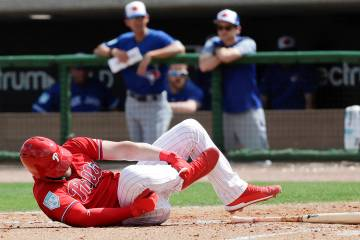 Philadelphia Phillies' Bryce Harper rolls on the dirt holding his leg after getting hit by a pitch against the Toronto Blue Jays during the sixth inning in a spring training baseball game, Friday, ...