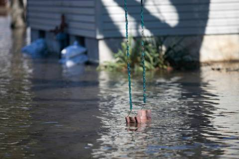 A swing hung from a tree dips into flood waters on Shore Drive Saturday, March 16, 2019, in Machesney Park, Ill. Many rivers and creeks in the Midwest are at record levels after days of snow and r ...