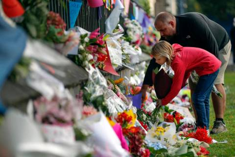 Mourners lay flowers on a wall at the Botanical Gardens in Christchurch, New Zealand, Saturday, March 16, 2019. New Zealand's stricken residents reached out to Muslims in their neighborhoods and a ...