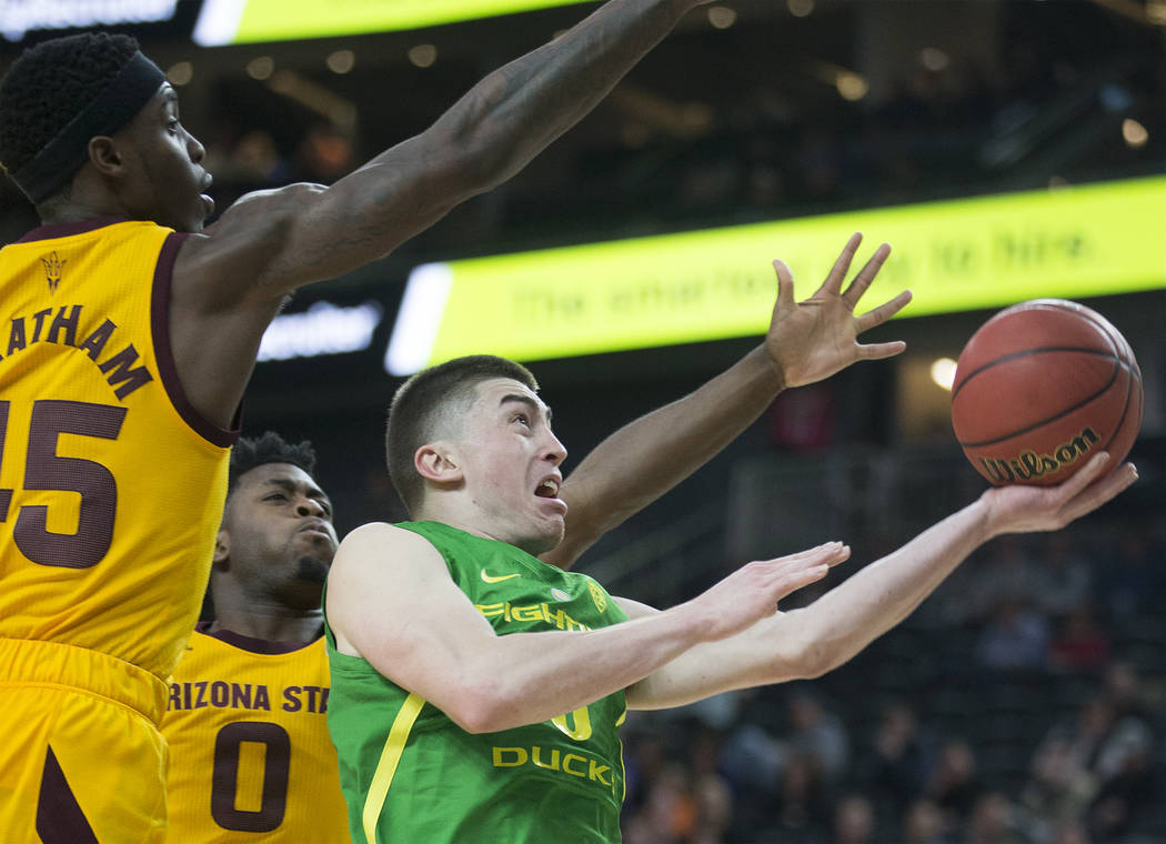 Oregon junior guard Payton Pritchard (3) slices to the rim past Arizona State senior forward Zylan Cheatham (45) and freshman guard Luguentz Dort (0) in the second half during the semifinal game o ...