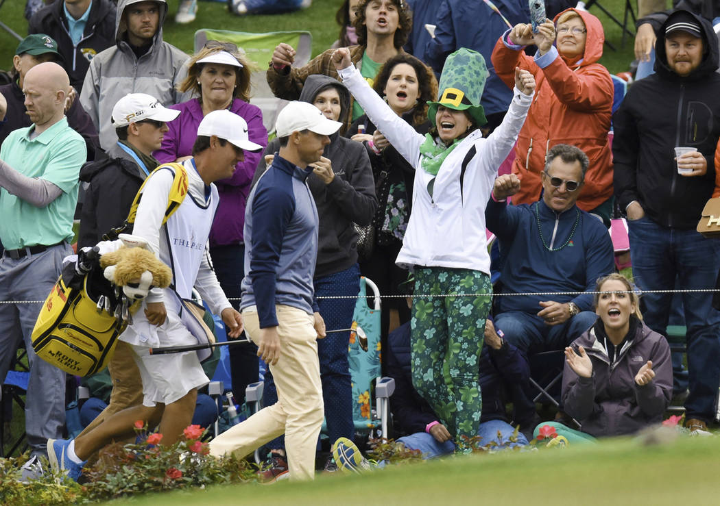 Rory McIlroy, of Northern Ireland, walks past cheering spectators on his way to the 17th green Sunday afternoon during the final round of The Players Championship golf tournament Sunday, March 17, ...
