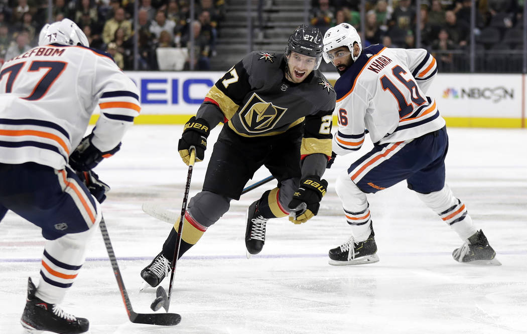 Vegas Golden Knights defenseman Shea Theodore (27) skates with the puck through Edmonton Oilers defenders during the second period of an NHL hockey game Sunday, March 17, 2019, in Las Vegas. (AP P ...