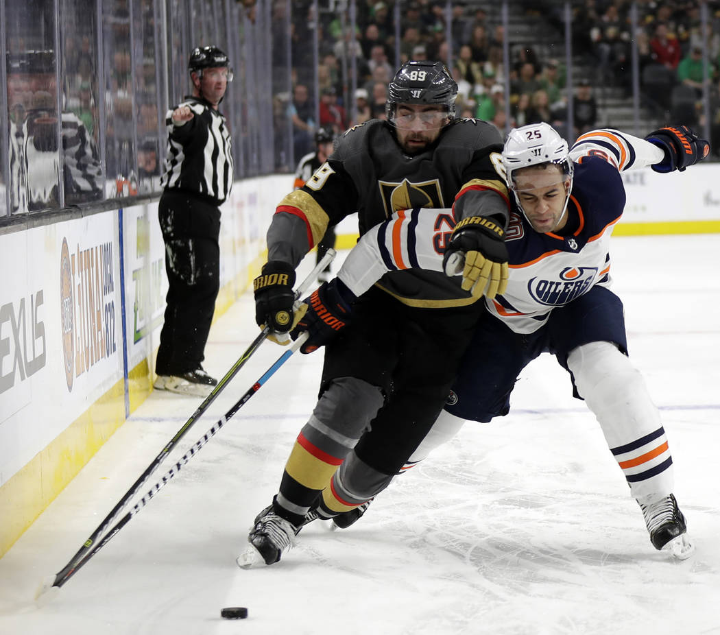 Vegas Golden Knights right wing Alex Tuch and Edmonton Oilers defenseman Darnell Nurse compete for control of the puck during the second period of an NHL hockey game Sunday, March 17, 2019, in Las ...