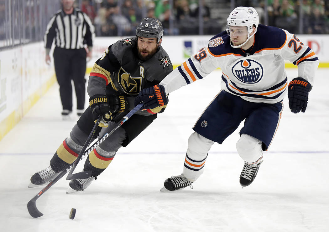 Vegas Golden Knights defenseman Deryk Engelland (5) skates with the puck as Edmonton Oilers left wing Leon Draisaitl defends during the second period of an NHL hockey game Sunday, March 17, 2019, ...
